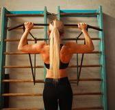 Sporty athlete woman exercising doing pull-ups in gym from back Stock Image