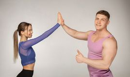 Sporty attractive couple in trendy sportswear giving high five to each other stock image