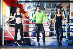 Young handsome trainer with young and sporty woman in the gym. Sport concept. royalty free stock images