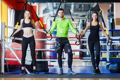 Young handsome trainer with young and sporty woman in the gym. Sport concept. royalty free stock image