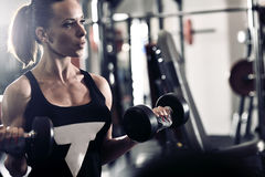 Sporty attractive woman in the gym with exercise equipment Stock Photography