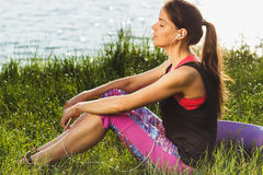 Sporty attractive woman on the lakes coast listening music Royalty Free Stock Photography