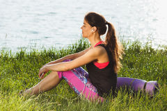 Sporty attractive woman on the lakes coast listening music Royalty Free Stock Image