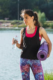 Sporty attractive woman on the lakes coast with a mat Royalty Free Stock Photos