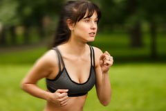Sporty attractive woman running outdoor in green park background Royalty Free Stock Photo