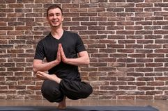 Sporty attractive young man working out, yoga, pilates, fitness training, balance in Eka pada ardha padmasana pose over brick wall royalty free stock image