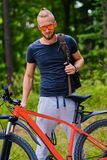 A man sits on a red mountain bicycle outdoor. stock photography