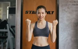 Sporty beautiful asian woman posture standing and lifting up her arms and exercises muscle at gym stock photography