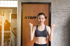 Sporty beautiful asian woman posture standing and lifting up her arms and exercises muscle at gym,Happy and smiling royalty free stock photos