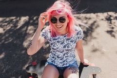 Sporty beautiful smiling woman with blowing pink hair wearing black sunglasses, with tattoo, sitting on her long board royalty free stock photography