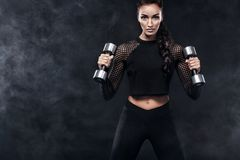 Sporty beautiful woman with dumbbells makes fitness exercising at black background to stay fit Royalty Free Stock Images