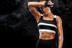 Sporty beautiful afro-american model, woman in sportwear makes fitness exercising at black background to stay fit. Sporty beautiful woman exercising to stay fit Royalty Free Stock Photography