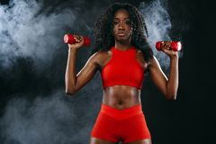 Sporty fit black skin woman in red sportswear, athlete with dumbbells makes fitness exercising on dark background. royalty free stock photo