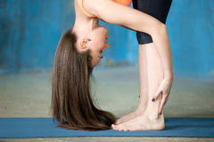 Sporty beautiful young woman Doing Standing forward bend pose. Portrait of beautiful young woman enjoying yoga indoors. Yogi girl working out in grunge interior Stock Photo