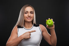 Sporty beefy woman holding green apple royalty free stock image
