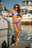 Sporty bikini model with perfect body standing on the pier Royalty Free Stock Photos