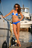 Sporty bikini model with perfect body standing on the pier Royalty Free Stock Image