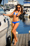 Sporty bikini model with perfect body standing on the pier Stock Images