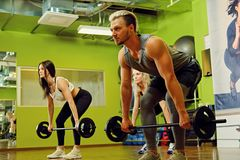 Sporty male and two females doing squats with barbells in a gym. stock images