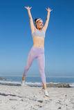 Sporty blonde on the beach jumping up. On a sunny day Stock Images