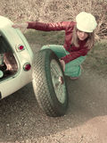 Sporty Blonde Changing Tire  Stock Images