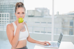 Sporty blonde eating apple while using laptop Royalty Free Stock Photography
