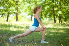 Sporty blonde girl doing fitness outdoor. Pretty young blonde girl doing aerobics or yoga outdoor, in the forest royalty free stock photo