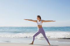 Sporty blonde in warrior pose on the beach Royalty Free Stock Image