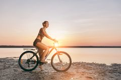 A sporty blonde woman in a colorful suit rides a bike in a desert area near the water on a sunny summer day. Fitness concept. Blue. The sporty blonde woman in a Royalty Free Stock Image