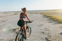 A sporty blonde woman in a colorful suit rides a bike in a desert area on a sunny summer day. Fitness concept. Back view Royalty Free Stock Photography