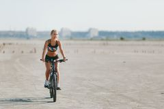 A sporty blonde woman in a colorful suit rides a bike in a desert area on a sunny summer day. Fitness concept. Blue sky background Royalty Free Stock Photos