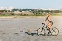 A sporty blonde woman in a colorful suit rides a bike at fast speed in a desert area on a sunny summer day. Fitness concept. Blur Stock Photos
