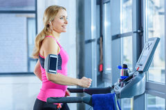 Sporty blonde woman exercising on treadmill in gym Royalty Free Stock Images