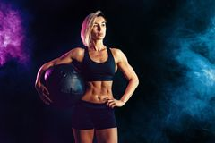 Sporty blonde woman in fashionable sportswear posing with medicine ball. Photo of muscular woman on dark background with royalty free stock images