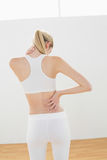 Sporty blonde woman touching her injured nape Royalty Free Stock Photo