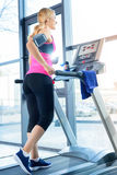 Sporty blonde woman training on treadmill in gym Royalty Free Stock Photo