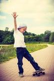 Sporty boy child skateboarding outdoor. Stock Photos