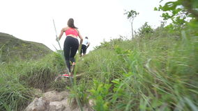 Sporty boy and girl running on difficult high mountain track. Woman and man work out in nature stock video footage