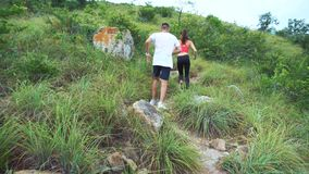 Sporty boy and girl running on mountain track. Woman and man work out in nature stock video