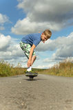 Sporty boy riding on the road waveborde Royalty Free Stock Photos