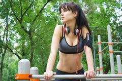 Sporty brunetki młoda dziewczyna z hełmofonami i smartphone na barach Fotografia Royalty Free