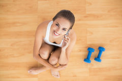 Sporty brunette holding a mobile phone and sitting next to dumbbells Royalty Free Stock Photo