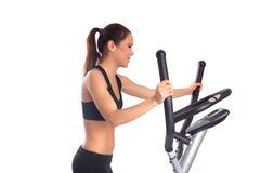 Sporty brunette woman on  exerciser Stock Images