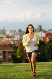 Sporty brunette woman running in city park Royalty Free Stock Images