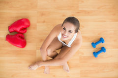 Sporty brunette woman sitting next to red boxing gloves and dumbbells Stock Photo