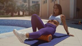 Sporty brunette woman training on mat outdoor summer day, massaging and stretch