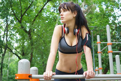 Sporty brunette young girl with headphones and smartphone on bars. Sporty brunette young girl with headphones and smartphone practicing on bars on summer day Royalty Free Stock Photography