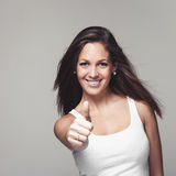 Sporty busty young woman giving a thumbs up Royalty Free Stock Image