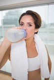 Sporty calm brunette drinking from water bottle Stock Photos