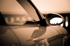 Sporty car rearview mirror with this black and white reflection royalty free stock photography